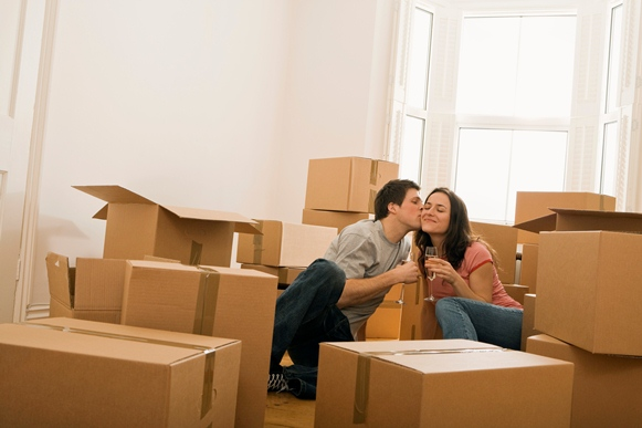 Romantic couple with champagne and moving boxes